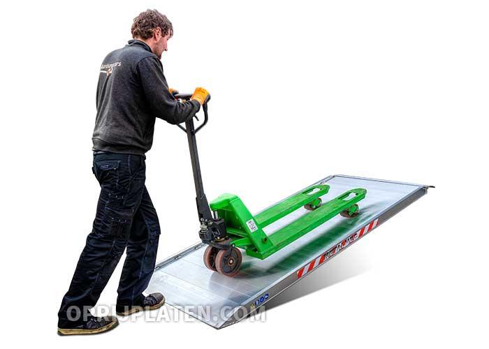 Persoon met palletwagen op oprijplaat
